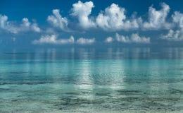 De schitterende verbazende het uitnodigen mening van vroege ochtend oceaan en witte pluizige wolken dacht op waterachtergrond na Stock Afbeelding