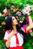 De schitterende vrouw bekijkt mooie bloemen en houdt het bij een park royalty-vrije stock fotografie