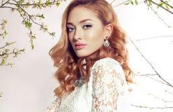 De schitterende vrouw met blond krullend haar draagt elegant kleding en juweel Royalty-vrije Stock Foto