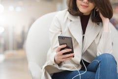 De schitterende vrouw in smartphone van het trenchcoatgebruik luistert via oor phon Royalty-vrije Stock Foto's