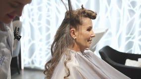 De schitterende vrouw zit en treft aan huwelijk met hulp van hoge professionele stilist en kapper voorbereidingen stock video