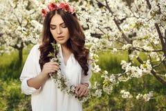 De schitterende vrouwen met het donkere haar stellen in de lente tuinieren Stock Foto