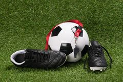 De schoenen en de bal voor het spelen van voetbal liggen op een groen gazon stock foto