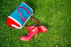 De schoenen en de handtas leggen op het gras, de schoenen van vrouwen stock afbeelding
