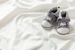 De schoenen van de babyjongen op wit satijn, exemplaarruimte royalty-vrije stock afbeelding