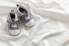 De schoenen van de babyjongen op wit satijn, exemplaarruimte stock afbeeldingen
