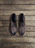 De schoenen van bruine mensen op een houten achtergrond Royalty-vrije Stock Afbeelding