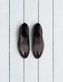 De schoenen van bruine mensen op een houten achtergrond Royalty-vrije Stock Foto