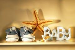 De schoenen van de baby op de plank stock afbeelding