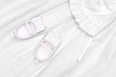 De schoenen van de baby op kleding Stock Foto's
