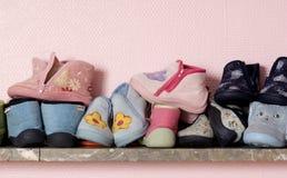 De schoenen van de baby op planken Stock Foto's