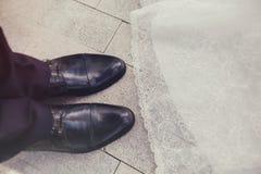 De schoenen van de bruidegom en de boord van de bruid kleden close-up royalty-vrije stock foto