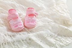 De schoenen van het babymeisje op wit kant, exemplaarruimte stock afbeeldingen