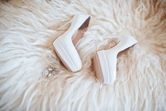 De schoenen van het bruidhuwelijk met hoge hielen en zilveren briljante oorring Royalty-vrije Stock Foto's