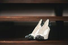 De schoenen van het bruidhuwelijk met hoge hielen en zilveren briljante oorringen op schapen` s kleding Royalty-vrije Stock Foto