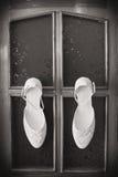 De schoenen van het bruidhuwelijk met hoge hielen en zilveren briljante oorringen op schapen` s kleding Stock Foto