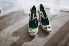 De schoenen van het bruidhuwelijk met hoge hielen en zilveren briljante oorringen op schapen` s kleding Royalty-vrije Stock Fotografie