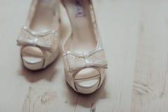 De schoenen van het bruidhuwelijk met hoge hielen en zilveren briljante oorringen op schapen` s kleding Royalty-vrije Stock Afbeeldingen
