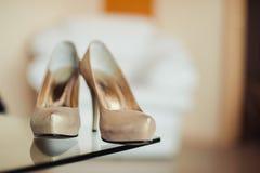 De schoenen van het bruidhuwelijk met hoge hielen en zilveren briljante oorringen op schapen` s kleding Stock Afbeelding