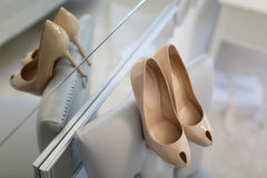 De schoenen van het bruidhuwelijk met hoge hielen en zilveren briljante oorringen op schapen` s kleding Stock Fotografie