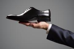 De schoenen van het de luxeleer van de zakenmanholding ter beschikking Stock Fotografie