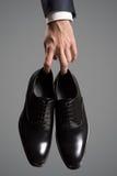 De schoenen van het de luxeleer van de zakenmanholding ter beschikking Stock Foto