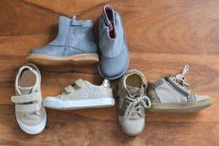 De schoenen van het verschillende meisje op een houten achtergrond royalty-vrije stock fotografie