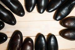 De schoenen van vele leermensen op houten achtergrond Royalty-vrije Stock Afbeeldingen