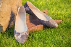 De schoenen van vrouwen, balletvlakten op gras, militaire stijl stock afbeelding