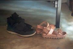 De schoenen van vrouwen die voor de schoenen van mannen worden geplaatst stock fotografie