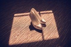 de schoenen van vrouwen op een houten Bruidschoenen van achtergrond lichte glanzende hielschoenen en een klein boeket royalty-vrije stock foto's