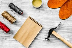 De schoenmaker neemt orde Notebok op grijs houten bureau achtergrond hoogste meningsmodel stock fotografie