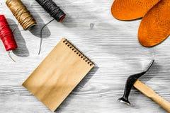 De schoenmaker neemt orde Notebok op grijs houten bureau achtergrond hoogste meningsmodel stock foto's