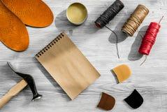 De schoenmaker neemt orde Notebok op grijs houten bureau achtergrond hoogste meningsmodel stock afbeelding