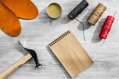 De schoenmaker neemt orde Notebok op grijs houten bureau achtergrond hoogste meningsmodel royalty-vrije stock afbeelding