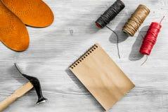 De schoenmaker neemt orde Notebok op grijs houten bureau achtergrond hoogste meningsmodel royalty-vrije stock afbeeldingen