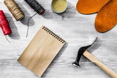 De schoenmaker neemt orde Notebok op grijze houten bureaubovenkant als achtergrond royalty-vrije stock afbeelding