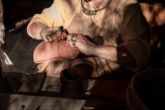 De schoenmeester naait schoenen en leer stock fotografie