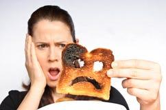 De schokvrouw houdt een gebrande plak van toost stock foto