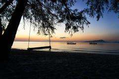 De schommeling bij mooie zonsopgang op tropische strandkoh rong modelleert met longtailboten terwijl de zon uitgaat royalty-vrije stock foto's