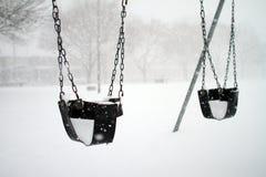 De schommeling van de baby die met sneeuw wordt behandeld Stock Fotografie