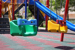 De schommeling van Multi-colored kinderen op de speelplaats openlucht Stock Fotografie
