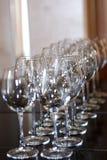 De schone glanzende tribune van wijnglazen op een rij stock afbeelding