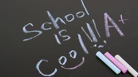 De school van het inschrijvings multicolored krijt is koel, wit en roze krijt in het kader Appel en melk tegen een bord met terug stock video