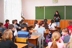 De schooljonge geitjes in de klaslokaalzitting bij hun bureaus en luisteren aan de leraar royalty-vrije stock afbeelding