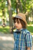 De schooljongen in een hoed en een band - de vlinder gaat op het park H stock afbeeldingen