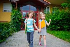 De schooljongen en het schoolmeisje zijn op de handen van een schoolpleinholding Stock Foto
