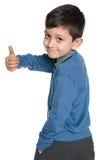 De schooljongen houdt haar duim tegen Stock Foto