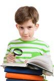De schooljongen leest boek met vergrootglas Stock Afbeeldingen