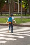 De schooljongen met een knapzak achter zijn rug loopt over de weg a royalty-vrije stock foto